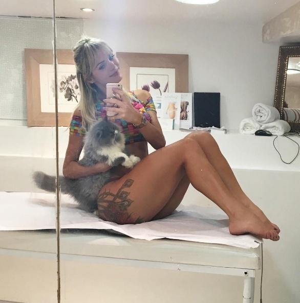 5.jul.2016 - Thalita Zampirolli também aparece em centros de estética para fortalecer a malhação com tratamentos na pele. Na imagem, a musa aparece com um gatinho e exibe a tatuagem nas coxas e bumbum