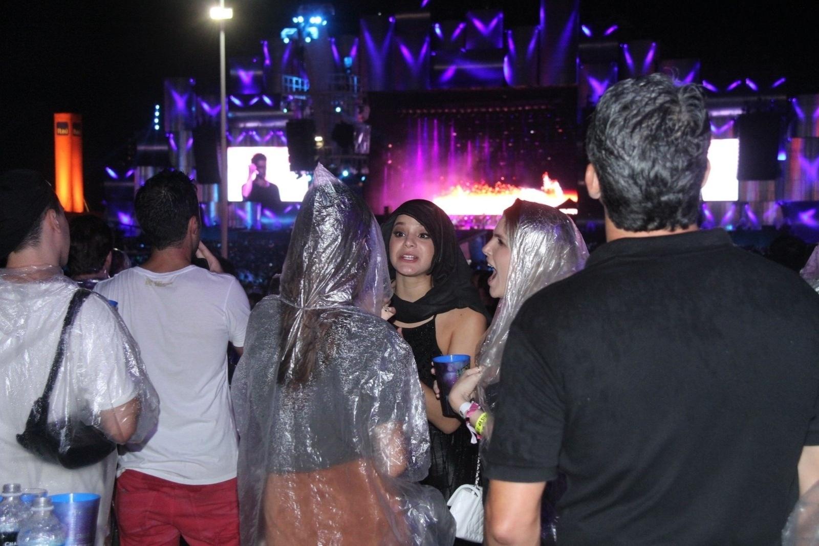 27.set.2015 - Em dia de chuva no Rock in Rio, Bruna Marquezine improvisa capa com casaco para curtir show na pista. Ela estava acompanhada por Thaila Ayala (de costas)