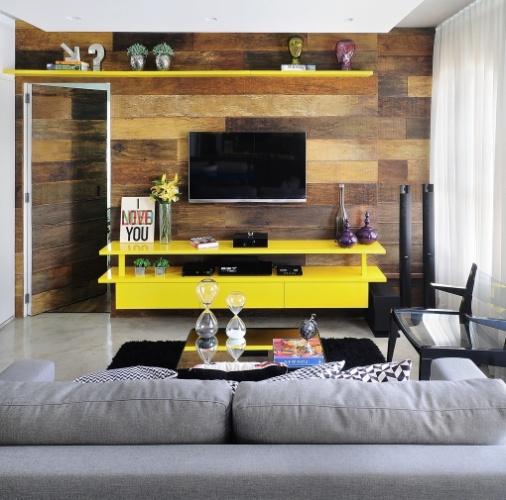 é o painel feito de madeira de demolição que sustenta a TV