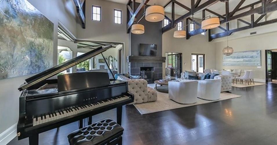 O piano é um dos destaques do segundo ambiente de estar da mansão que Britney Spears está vendendo, por R$ 32 milhões, na Califórnia, Estados Unidos. O espaço conta com móveis claros e blocados: em frente à lareira estão dois sofás em capitonê, duas poltronas e quatro luminária