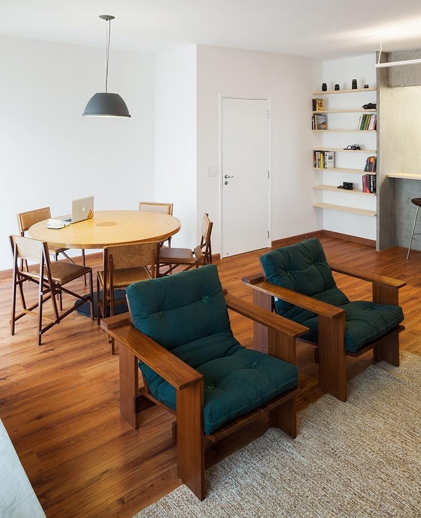 Na sala de estar do apartamento em São Paulo (SP), as duas poltronas PB, com desenho de Francisco Fanucci e produzidas pela Marcenaria Baraúna, têm estofado em futon. Perceba que para delimitar o estar do jantar, o Grupo Garoa Arquitetos recobriu o piso de madeira com um tapete em tom claro. A mesa Bolo de Rolo e as cadeiras Filó (peças do mesmo autor e marcenaria) compõem a área de refeições