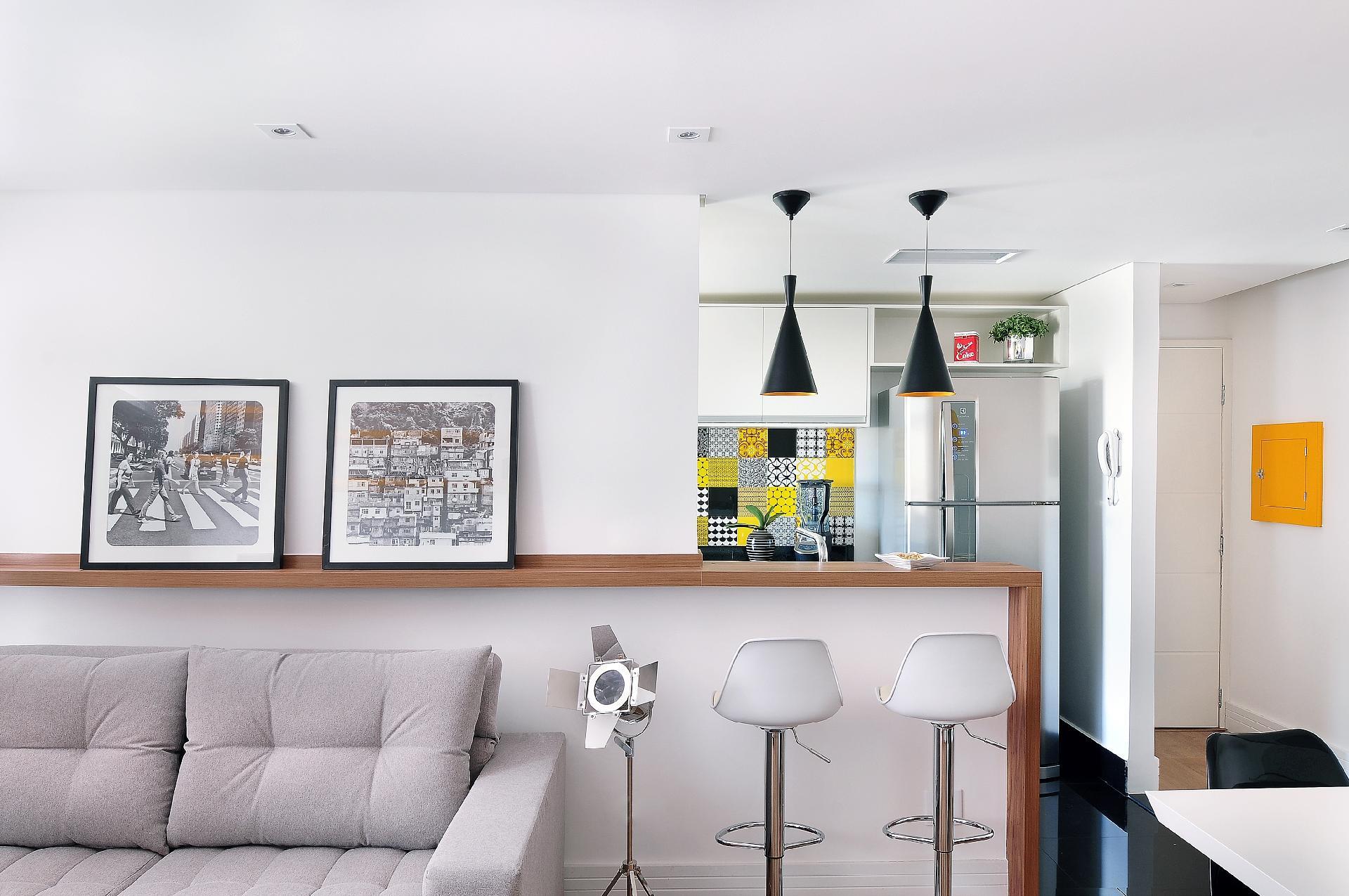 A bancada de madeira é acompanhada de duas banquetas que são usadas para as refeições. O sofá de dois lugares compõe a área de estar e, à direita, uma 'meia' parede resguarda parte da cozinha de quem chega à residência. A reforma capitaneada pelo escritório IBD pintou as paredes e portas de branco, o que proporcionou ar leve ao apê na Cantareira, em São Paulo