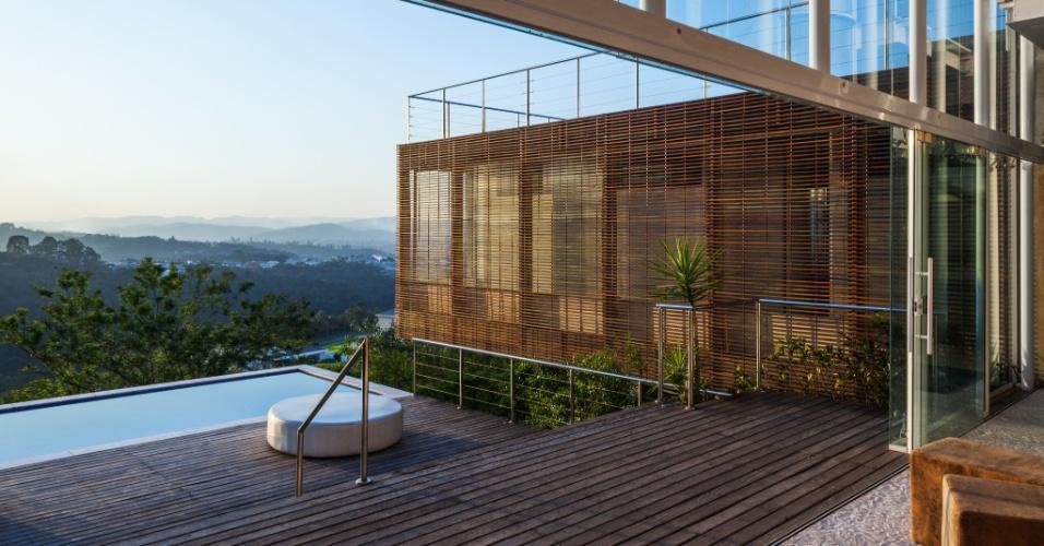A Casa Jatobá surge rasgando a paisagem de Santana do Parnaíba (SP). Projetada pelo escritório Gesto Arquitetura, tem, na face posterior, uma piscina com deck de madeira