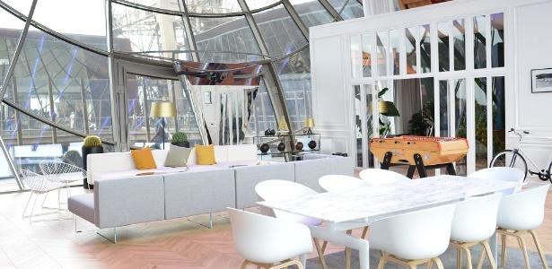 O espaço tem uma sala com mesa de jantar, sofás e uma TV de 140 polegadas