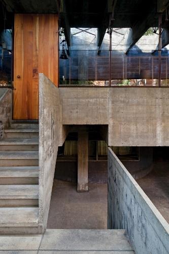 Na escada de acesso ao pavimento superior está um dos poucos elementos de madeira da casa: a porta de entrada. No piso inferior, destaque para um dos quarto pilares que suportam toda a construção. A superfície envidraçada reflete o beiral constituído por um pergolado, projetado pelo arquiteto Paulo Mendes da Rocha