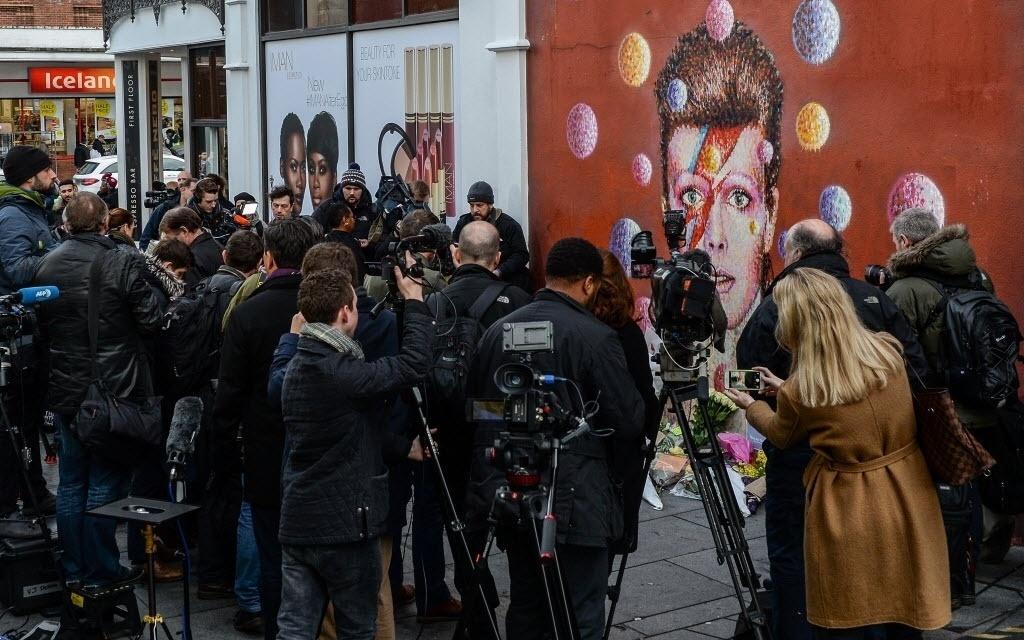 11.jan.2015 - Jornalistas se reúnem em frente a um mural de David Bowie feito por Jimmy C em Brixton, em Londres