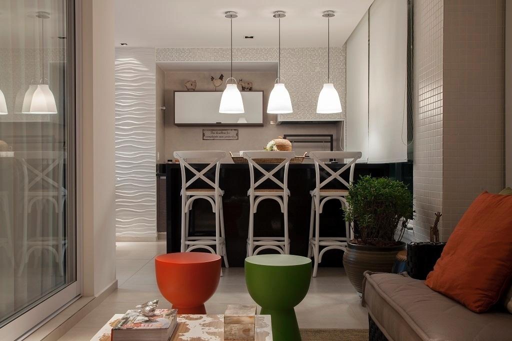 Na varanda gourmet, uma criação de Fernanda Pinheiro, a bancada escura conta com três banquetas brancas que combinam com a parede da churrasqueira, revestida com pastilhas de vidro e mármore. O espaço tem também uma área de estar com sofá