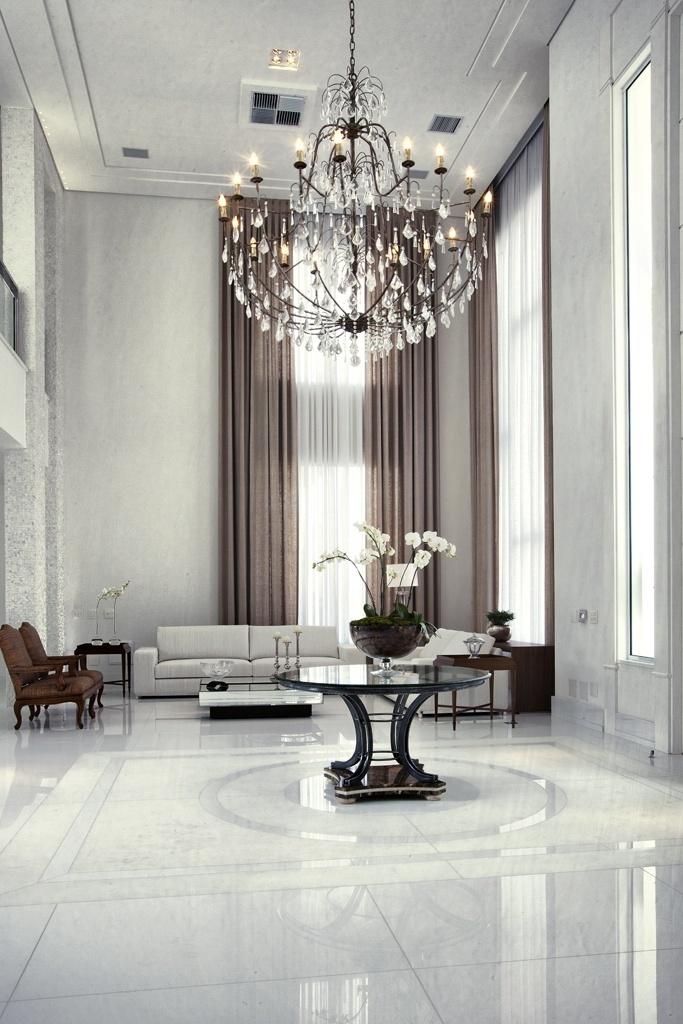 O lustre composto de cristais Swarovski tem estrutura de metal galvanizado e é resistente à maresia. Para complementar o estilo clássico, cortinas sintéticas se assemelham ao linho, mas são mais duráveis. O panejamento ressalta o pé-direito (6,5 m). No estar, os sofás, da Breton, foram revestidos com tecido náutico (Regatta), enquanto as poltronas em tecido-palha reforçam o aspecto clássico dos interiores desenhados por Bianka Mugnatto
