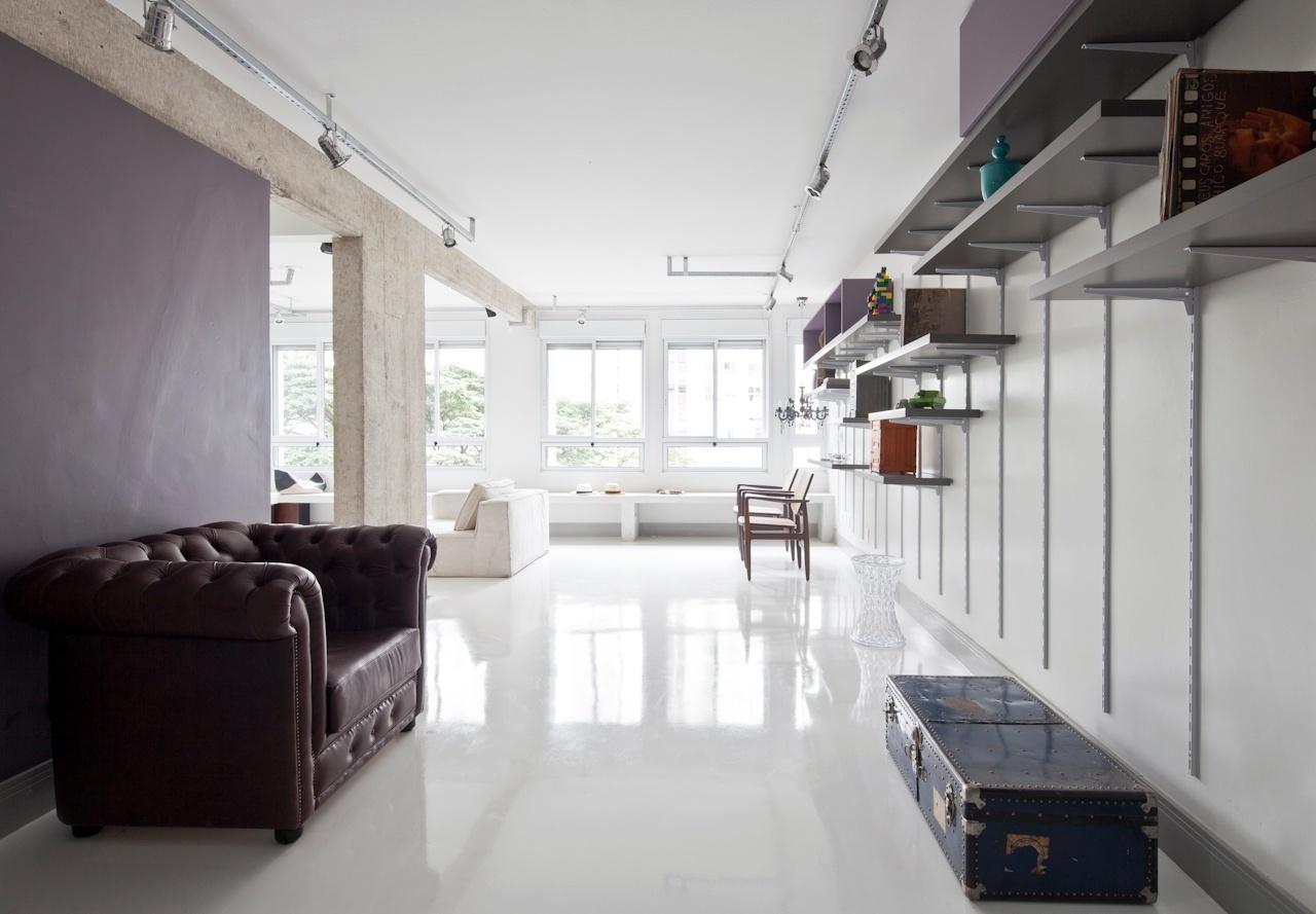 A sala de estar do apê Perdizes, com projeto de interiores do SuperLimão Studio, forma um L espaçoso e com decoração composta de poucos objetos, que permitem livre circulação e a recepção de muitos amigos. O piso é acabado com resina autonivelante e de paginação única, que dá continuidade ao ambiente