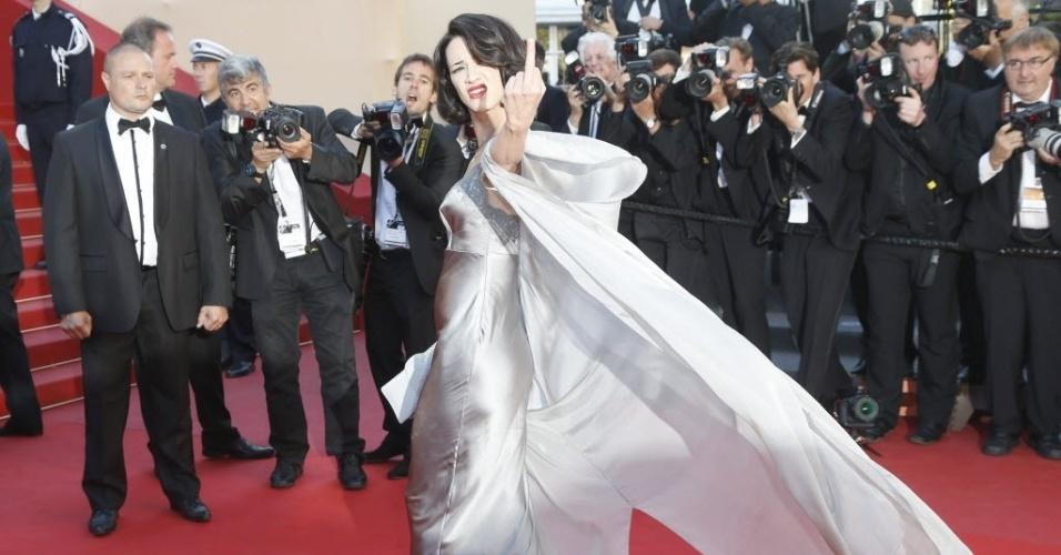 26.mai.2013 - A atriz italiana Asia Argento mostra o dedo médio para os fotógrafos ao cruzar o tapete vermelho da exibição do filme