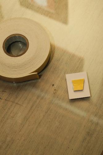 Coloque um pedaço de fita banana de mais ou menos 1 cm atrás de cada foto. A fita vai permitir que as fotos ganhem um certo relevo na composição