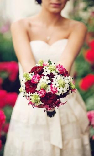 Imagem de noiva segurando buquê de flores coloridas