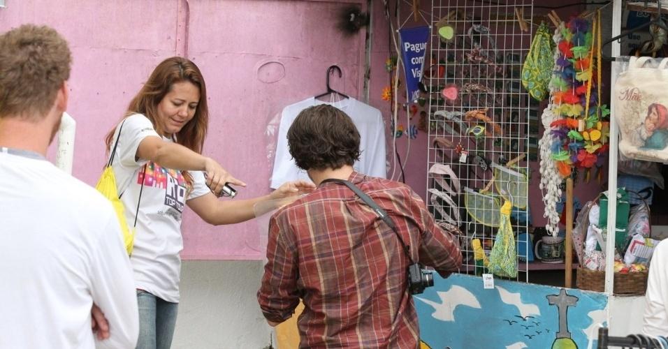 30.mai.2013 - Ator Bradley Cooper escolhe camiseta no Morro Dona Marta, no Rio de Janeiro