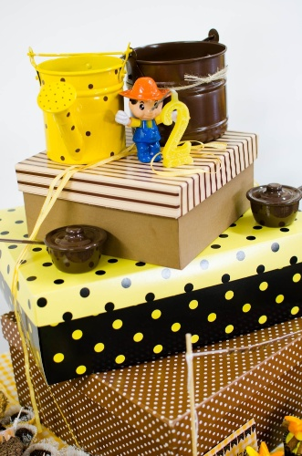 Embrulhados em papel e tecido, os pedaços do bolo de fubá foram inseridos em caixas que seguem a paleta de cores escolhida para a festa de Nino, em que predominam o marrom e o amarelo