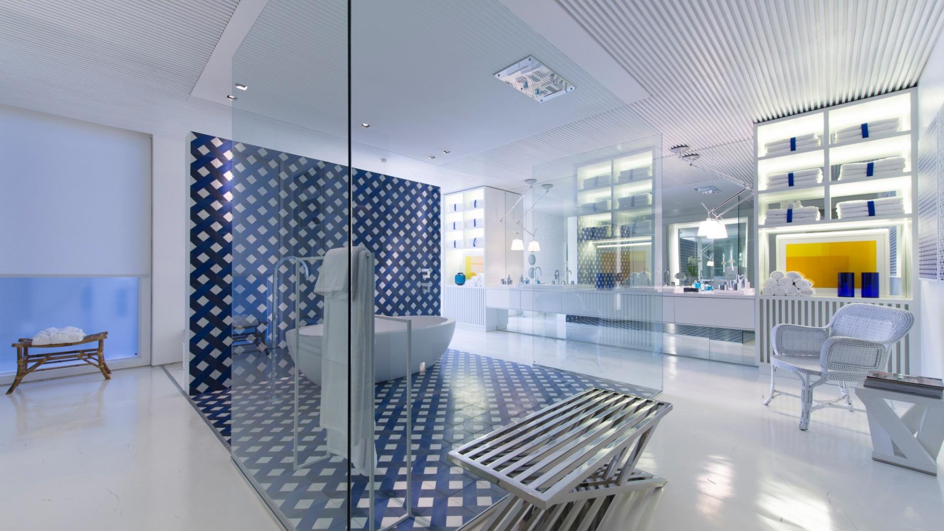 No amplo banheiro da Casa de Praia, Roberto Migotto centralizou a área de banho, delimitando-a através do piso e parede de revestimento em forma geométrica, dentro de uma
