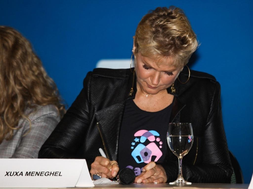 12.jun.2013 - Xuxa inaugura espaço social que arrecadará fundos para projetos de educação para crianças e adolescentes, em São Paulo. Durante a coletiva de imprensa, a apresentadora fez um desenho no cartão com seu nome