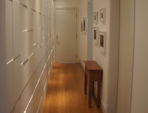 No corredor de acesso às suítes de um apartamento, o arquiteto Luis Navarro idealizou um roupeiro de um lado e do outro pendurou quadros. Repare que painéis desconexos em alto e baixo relevo, destacados pela iluminação, dão movimento e textura ao ambiente. Como os puxadores são embutidos, o trabalho surpreende as pessoas