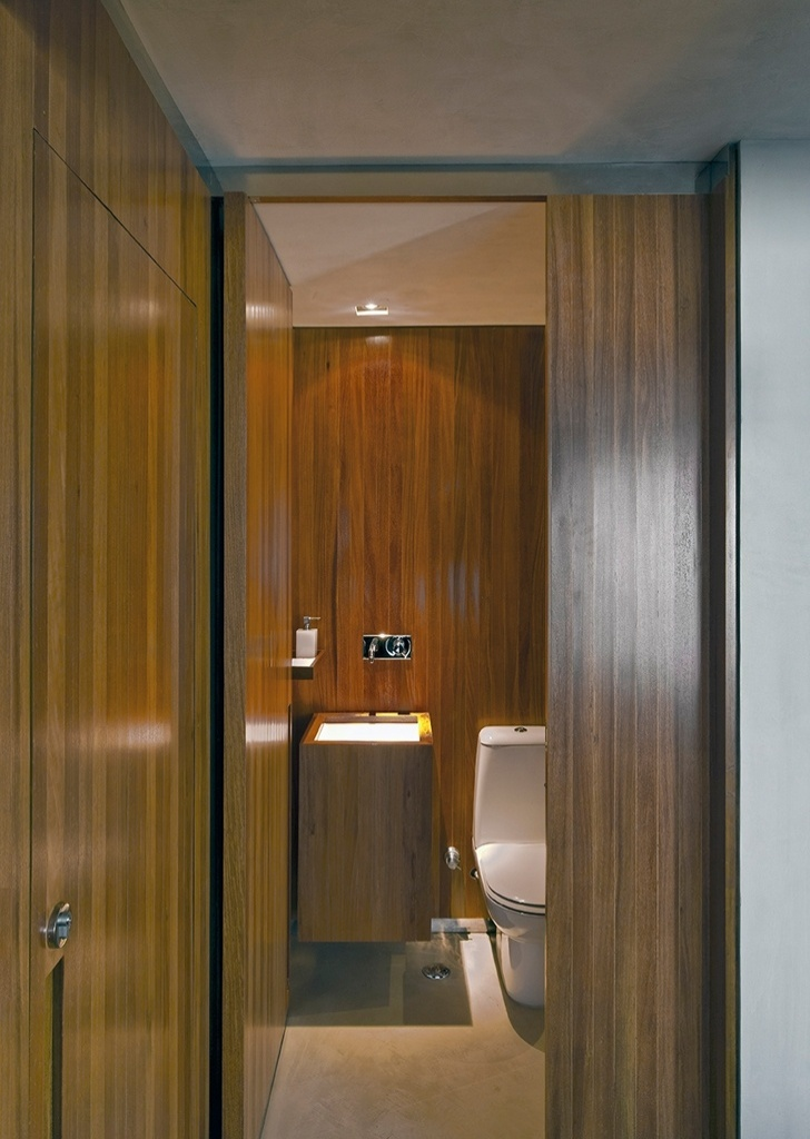 A madeira cumaru domina o espaço do lavabo, compondo porta, parede e gabinete da pia e contrastando com o cimento queimado do piso e do teto. O projeto de reforma do Loft Real Park é do arquiteto Diego Revollo