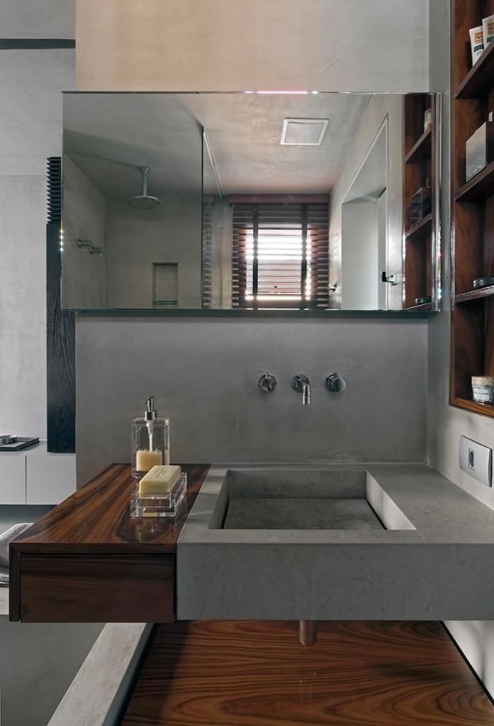 O banheiro recebeu detalhes em madeira pau-ferro na cuba, no gabinete e nas prateleiras, resultando num interessante efeito estético. O Loft Real Park teve o projeto de reforma assinado pelo arquiteto Diego Revollo