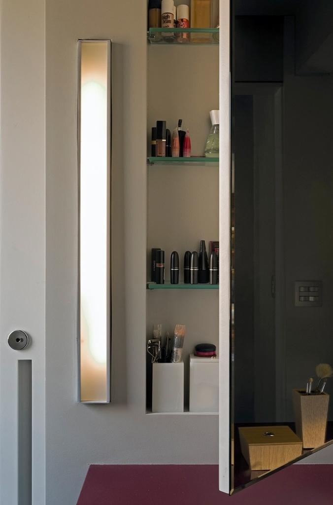 O espaço da esposa tem bancada na tonalidade fúcsia, num toque de cor em meio ao cinza. O armário com espelho guarda a maquiagem e os produtos de beleza e é iluminado pela luminária vertical da Bertolucci