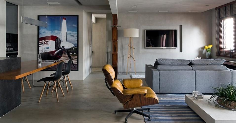 O living com ambientes integrados e revestimento em cimento queimado no piso, parede e teto forma uma caixa cinza. Destaque para a poltrona Charles Eames, da Artesian, e para a luminária Xote.Co, da Bertolucci, cuja base é um tripé de freijó. O projeto de reforma do Loft Real Park é do arquiteto Diego Revollo