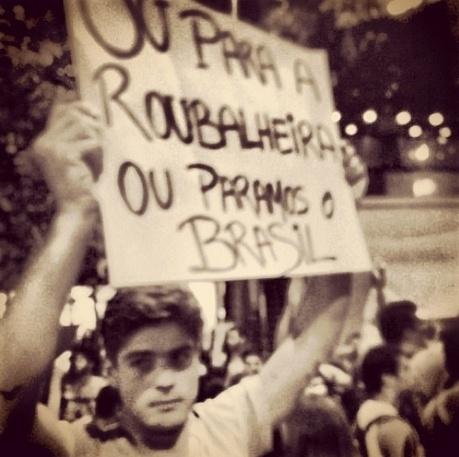 17.jun.2013 - O modelo Evandro Soldati leva cartaz durante manifestação no Rio de Janeiro