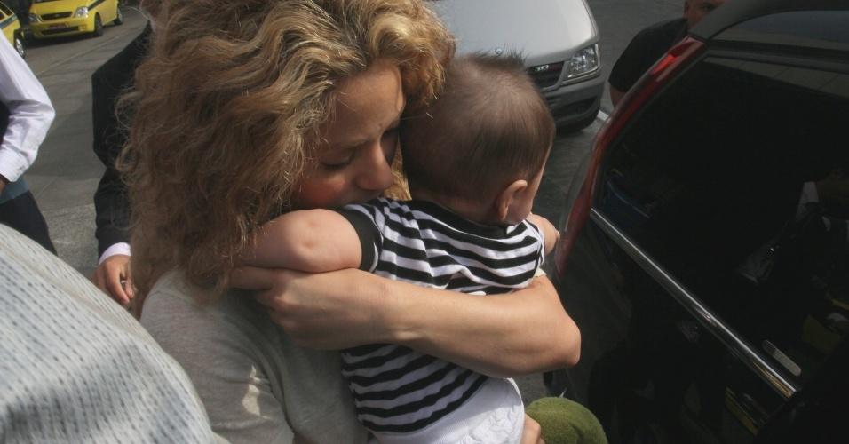 20.jun.2013 - A cantora colombiana Shakira desembarca no aeroporto internacional do Rio de Janeiro com o filho Milan. A cantora pega o bebê antes de entrar no carro, cercada por seguranças. Ela veio encontrar o namorado, o jogador da seleção espanhola Piqué