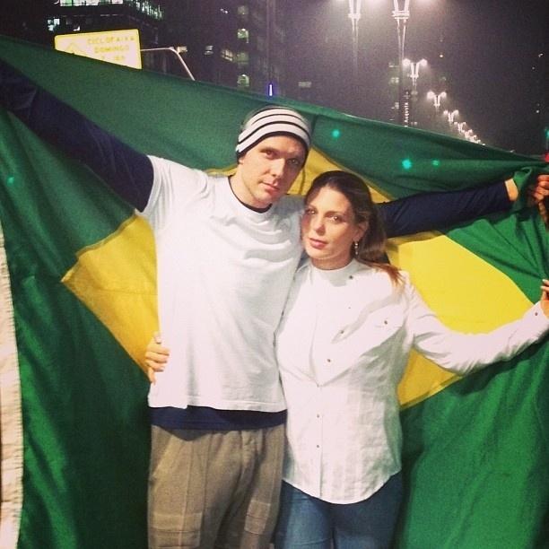 20.jun.2013 - Em São Paulo, o casal formado por Fernando Scherer e Sheilla Mello levou uma bandeira do Brasil