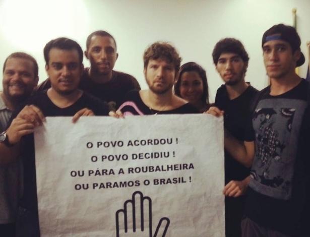 20. jun.2013 - O cantor Saulo Fernandes divulga foto com cartaz de protesto ao lado de amigos