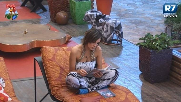 30.jun.2013 - Sem conseguir dormir, Andressa Urach lê o livro de instruções após receber o título de Fazendeira