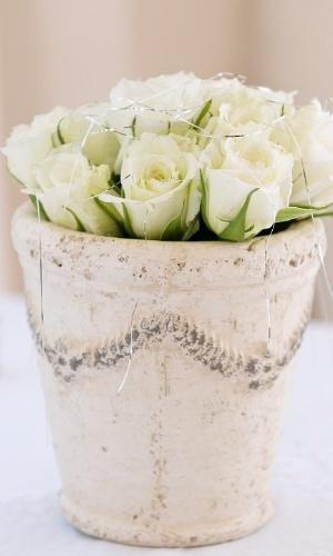 Centro de mesa com rosas brancas em vaso rústico. Vasos de plantas antigos, com a pintura gasta, ficam lindos com rosas dentro deles. A mistura proporciona um equilíbrio entre o delicado e o rústico e combina com casamentos ao ar livre
