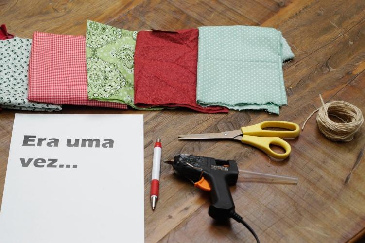 Para fazer as bandeirinhas, você vai precisar de retalhos de tecidos coloridos, o título impresso no papel sulfite, caneta, tesoura, barbante e pistola de cola quente