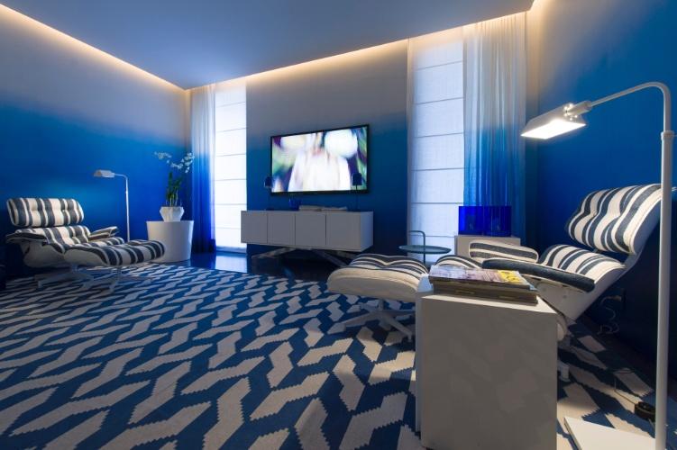 """A sala de TV da Casa de Praia, idealizada pelo arquiteto Roberto Migotto, também recebeu o azul """"klein"""" como base decorativa. A parede com um efeito degradê e o tapete estampado com formas geométricas se sobressaem. A 27ª Casa Cor SP segue até dia 21 de julho de 2013, no Jockey Club de São Paulo"""