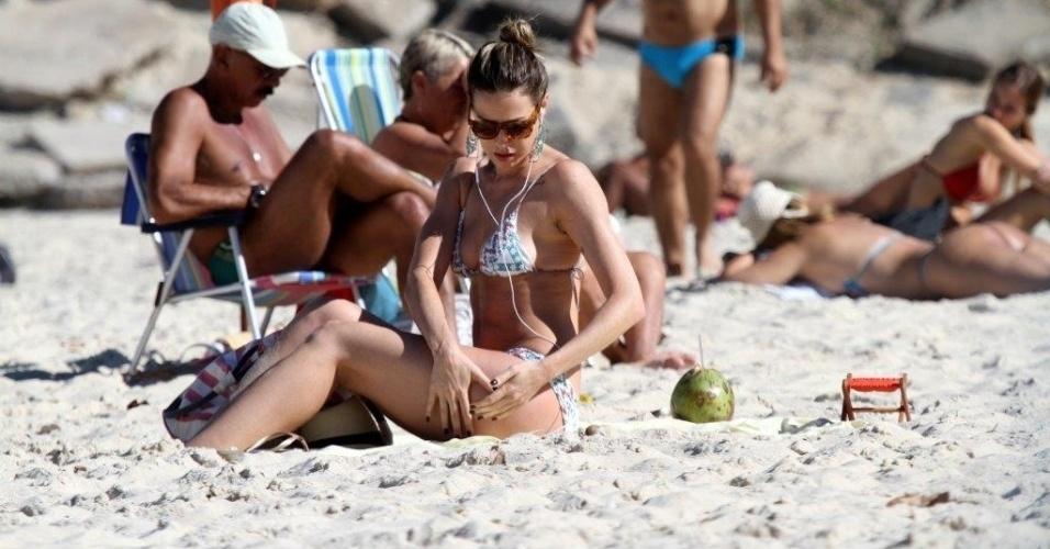 5.jul.2013 - Luana Piovani escuta música na praia do Leblon, na zona sul do Rio