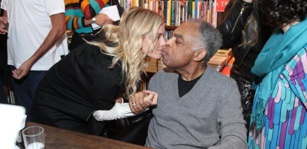 8.jul.2013 - A atriz Carolina Dieckmann dá selinho em Gilberto Gil durante o lançamento de