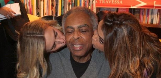 8.jul.2013 - Gilberto Gil recebe beijos da filha Preta Gil e de Carolina Dieckmann durante o lançamento de sua biografia,