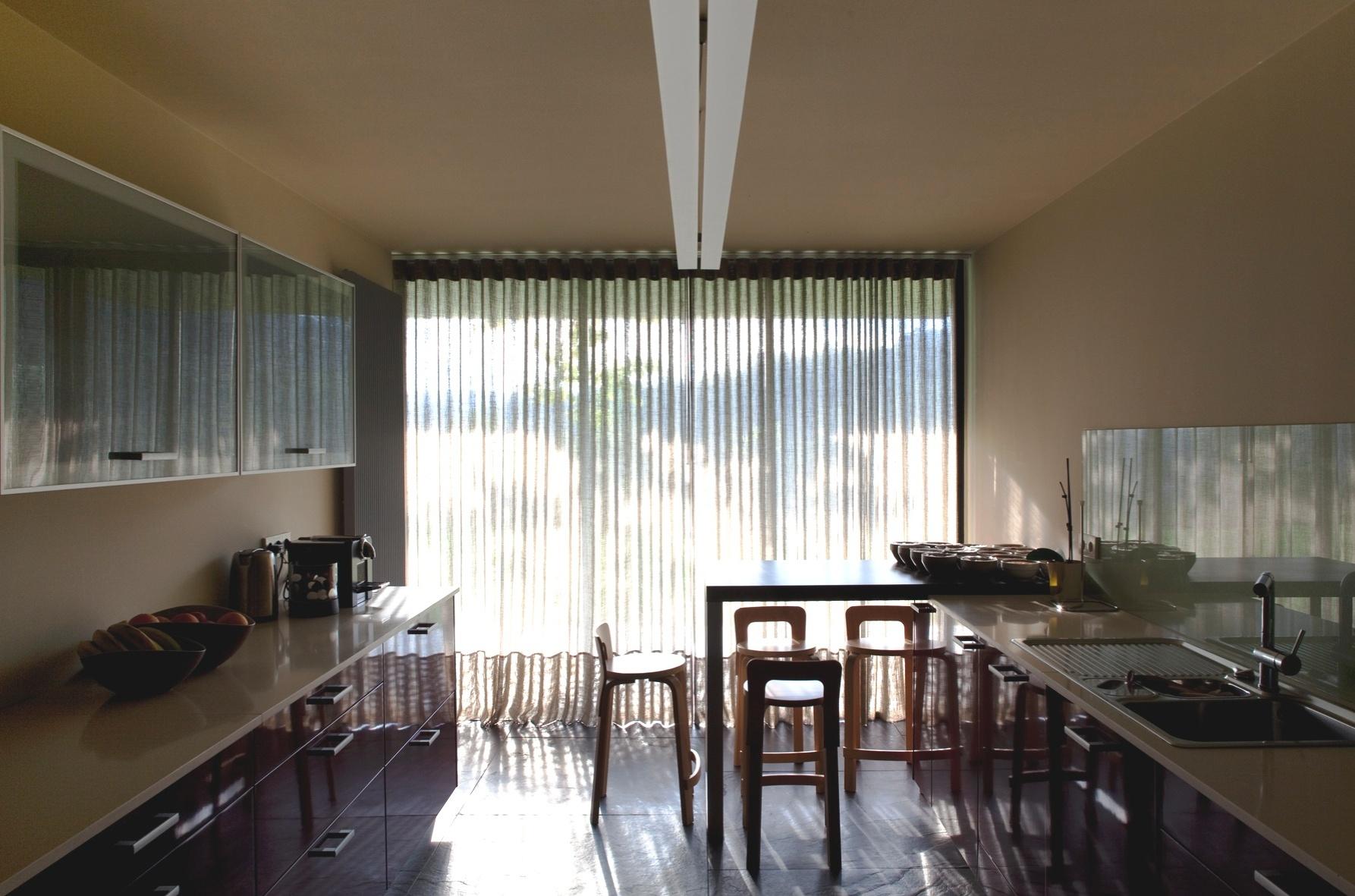Na RF House, a cozinha, assim como outros cômodos, recebeu piso de ardósia em grandes placas. O revestimento, além de coerente com a linguagem adotada pelo arquiteto Nuno Graça Moura, ajuda a refletir a luz
