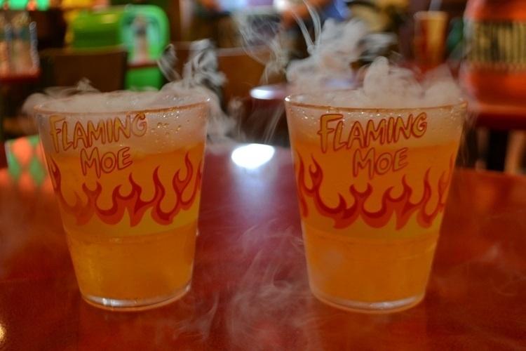 """O enigmático drink Flaming Moe ganha vida na nova área de alimentação do Universal Studios Florida, baseada na série de TV """"Os Simpsons"""". O copo pode ser levado de lembrança e apesar do aspecto """"perigoso"""" a bebida não leva álcool"""