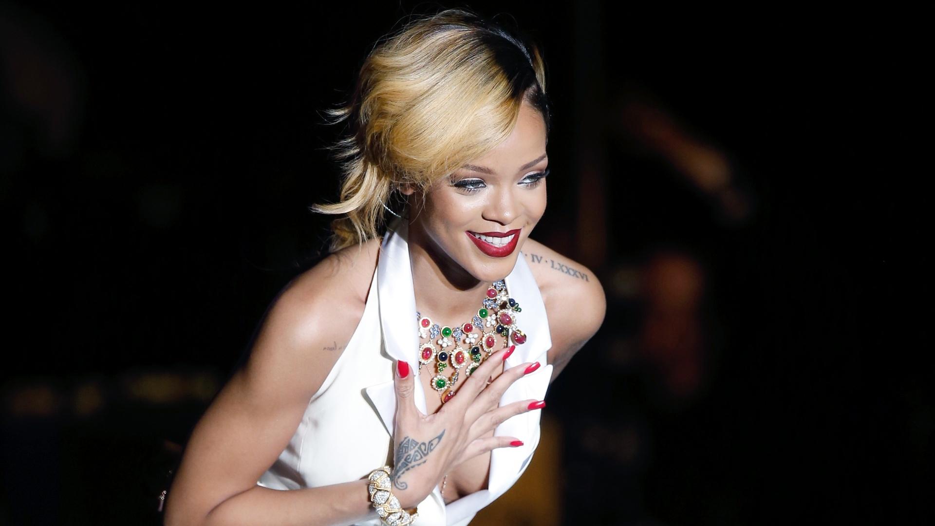 10.jul.2013 - De vestido decotado e parte do cabelo loiro, a cantora Rihanna fez show em Mônaco. A cantora apresentou novo show do disco,