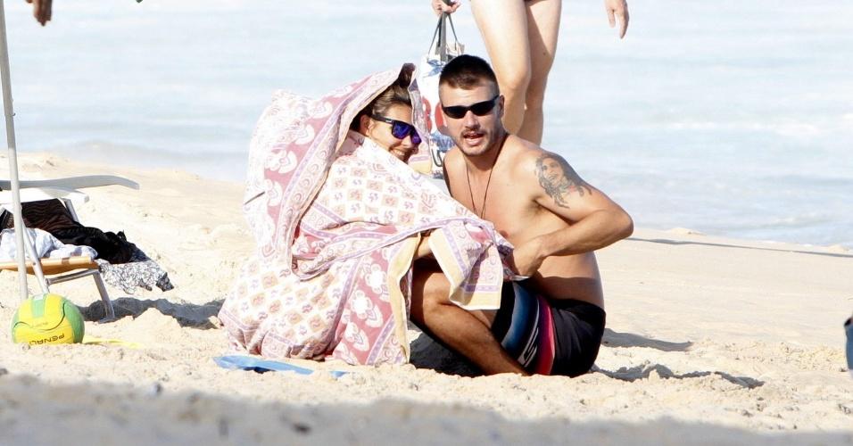 11.jul.2013 - Fernanda Lima e Rodrigo Hilbert curtiram praia no Leblon com os filhos, os gêmeos João e Francisco, de 5 anos. Com frio, Fernanda se enrolou em uma canga