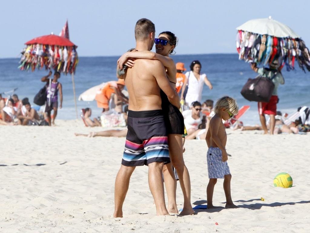 11.jul.2013 - Fernanda Lima e Rodrigo Hilbert curtiram praia no Leblon com os filhos, os gêmeos João e Francisco, de 5 anos. O casal não se intimidou com o paparazzo e trocou beijos e carícias
