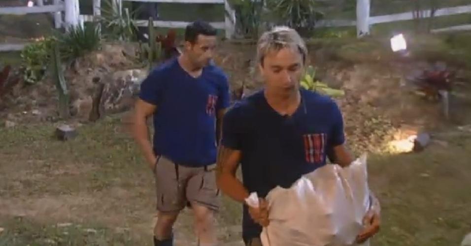 12.jul.2013 - De volta ao celeiro, Marcos Oliver e Paulo Nunes cortam lenha para o jantar