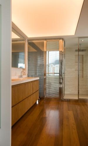 A área de banho da suíte do casal é ampla, com madeira predominante na bancada e no piso. O projeto de reforma e interiores, assinado pela arquiteta Izabela Lessa, interligou dois apartamentos, transformando em um dúplex, de 600 m², localizado em São Conrado (RJ)