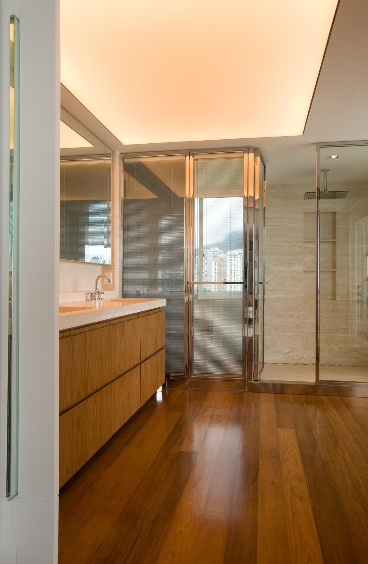 A área de banho da suíte do casal é ampla, com madeira predominante no revestimento da bancada e do piso. O projeto de reforma e interiores, assinado pela arquiteta Izabela Lessa, interligou dois apartamentos transformando-os em um dúplex, de 600 m², localizado em São Conrado (RJ)