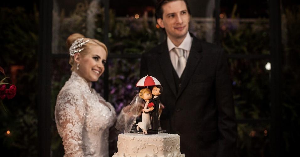 Hora de cortar o bolo: Monique e Diogo ao lado de suas miniaturas - que também têm um guarda-chuva temático