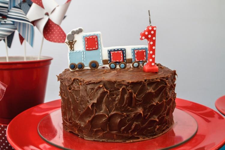 O suculento bolo coberto com uma camada generosa de chocolate é uma receita de Nika Linden (www.nikalinden.com.br). O trenzinho que enfeita o topo combina com a decoração da festa Brincadeiras de Menino, organizada pela (www.caraminholando.com.br)