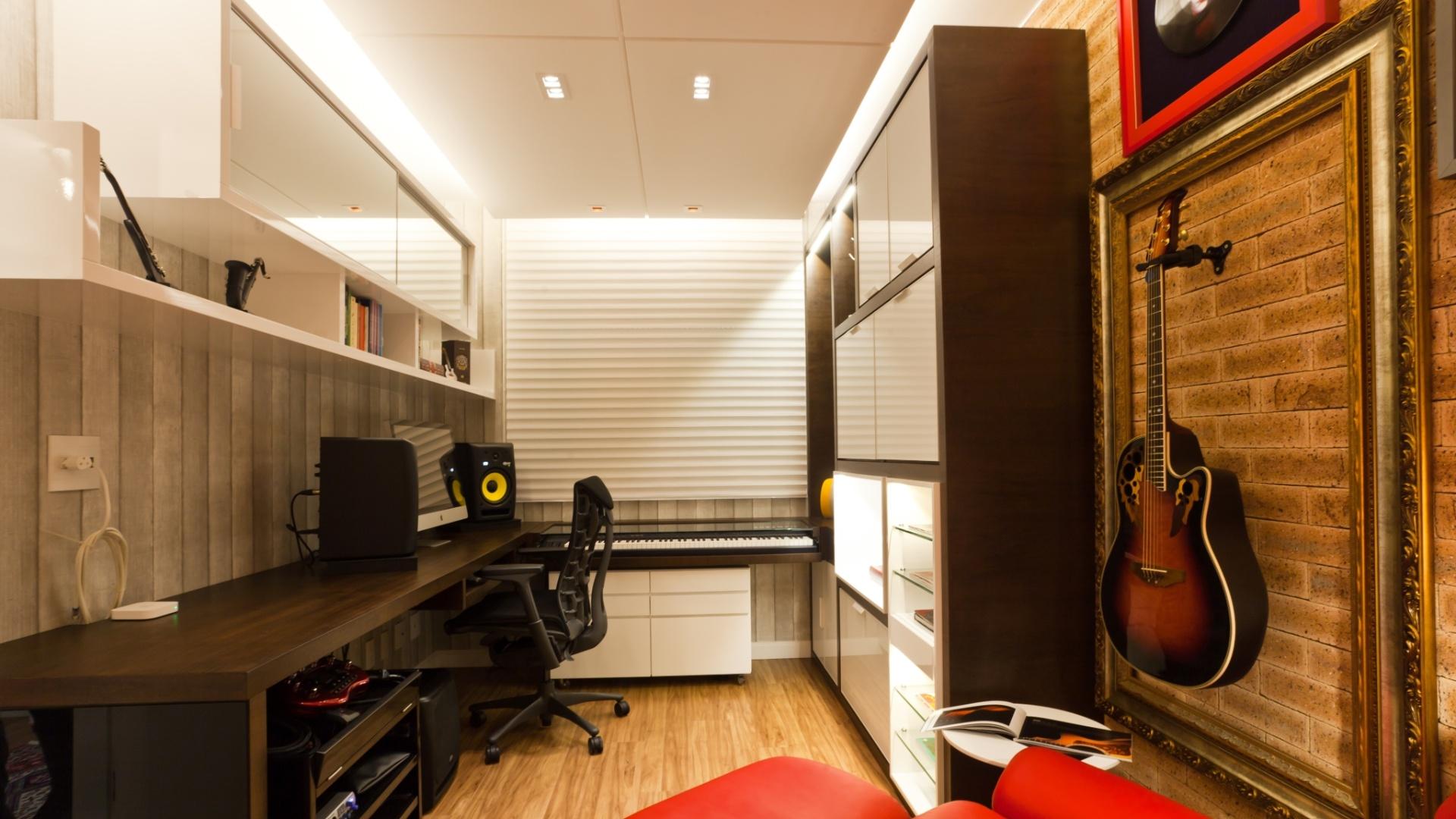 No apartamento projetado pela arquiteta Juliana Pippi, o estúdio de 11 m² ganhou isolamento acústico. A parede revestida de tijolo inglês, a persiana em tecido, o gesso rebaixado no teto e o revestimento interno em lã de rocha ajudam a impedir que o som incomode os vizinhos ou vaze para os outros cômodos. O papel de parede remete ao concreto e é outro diferencial da decoração