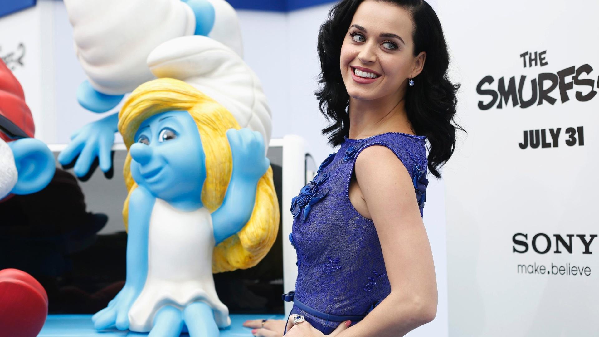 28.jul.2013 - Katy Perry, que dubla Smurfette, posa ao lado de sua personagem na pré-estreia do filme