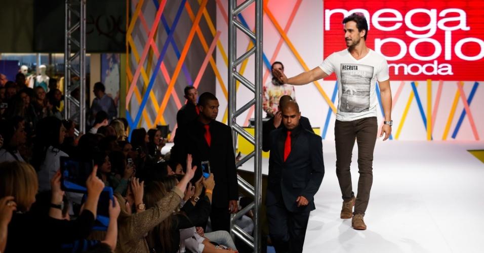 30.jul.2013 - O ator Julio Rocha acena para os fãs que assitem os desfiles do Mega Polo Moda
