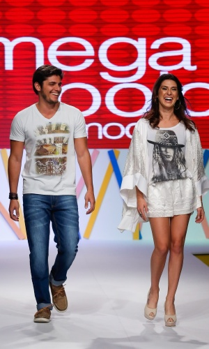 31.jul.2013 - Os atores Bruno Gissoni e Fernanda Paes Leme entram sorrindo ao final do desfile no evento do Mega Polo Moda